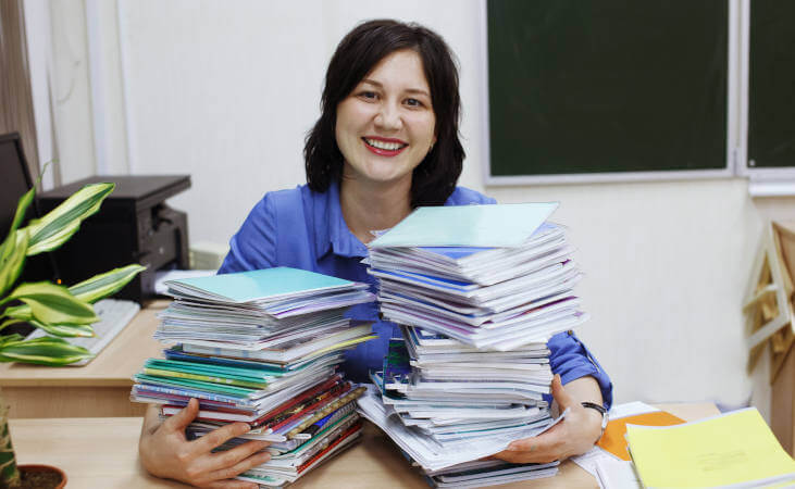 Teacher with piles of homework